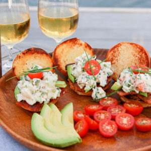 An over-the-top summer lobster roll garnished with bacon, avocado, tomato and lots of fresh herbs.